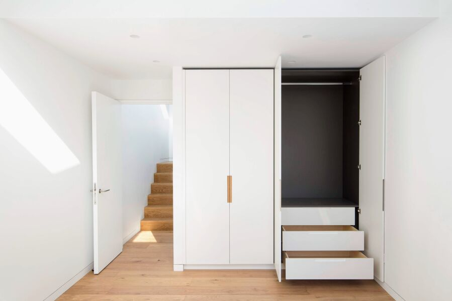 Wardrobe with PU lacquered fronts, oak inlay handles and dark grey melamine interior.