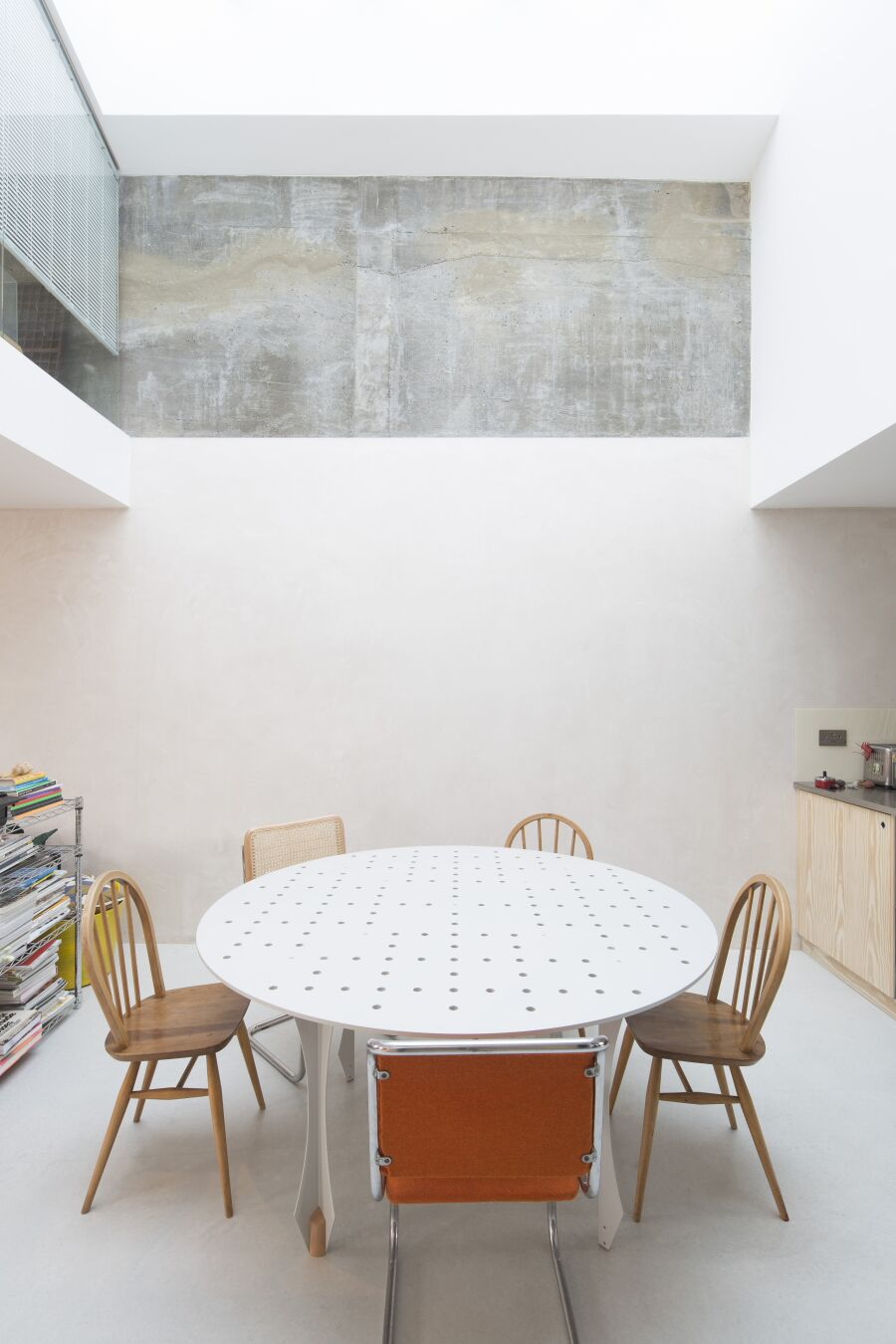 Perforated steel dining table in open plan dining area