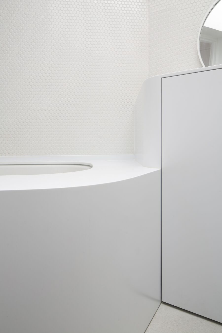 White curved Corian vanity unit and bath surround
