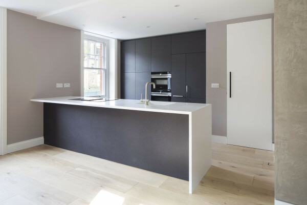 Modern kitchen with Corian worktop and black valchromat fronts.