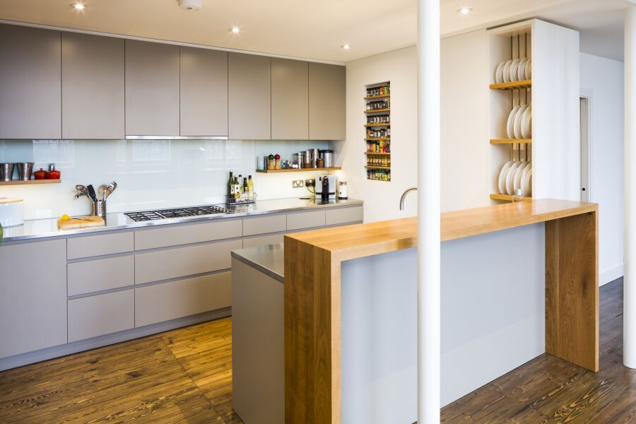 Modern kitchen with a mix of stainless steel and oak worktops, laminated plywood fronts and bespoke oak spice and plate racks.