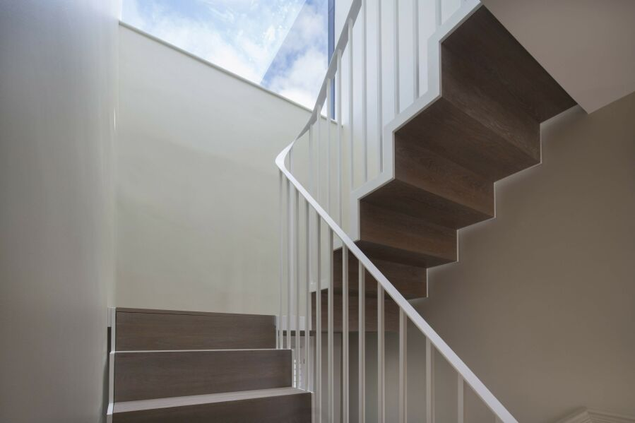 Powder-coated steel stairs with solid oak treads and riser on both sides.